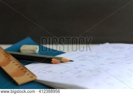 Two Simple Pencils On The Background Of A Notebook With Formulas, Rulers, Wash And School Blackboard