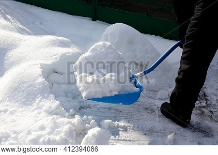 Man Shoveling  Snow Big Blue Shovel In The Suburb. Clearing A Road In Winter.