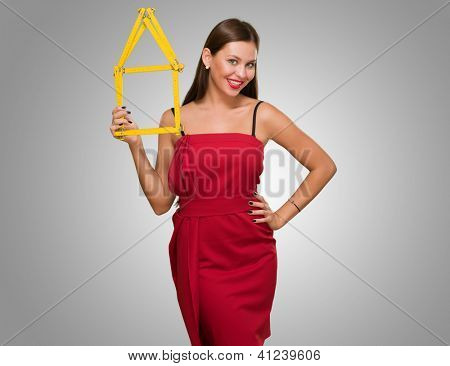 Happy Young Woman Holding House Frame against a grey background