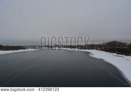 Winter Landscape With Unfrozen River And Town On The Bank In Cloudy Day