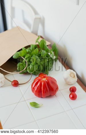 Shopping Food In Supermarket. Tomatoes, Garlic And Greens On White Table. Healthy Food Background.