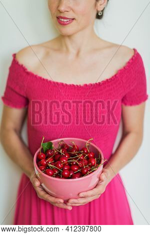 Closeup Cherry Berries In A Pink Bowl At Female Hands. Gardening, Agriculture, Harvest And Forest Co