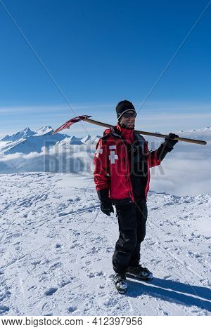 Ski Patroller On Snow Caped Mountain Is Standing Against Sun With A Red Rescue Jacket And A Shovel O