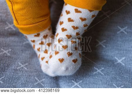 A Portrait Of Small Cute Baby Feet Wearing White Socks With Orange Hearts On Them. They Are Resting