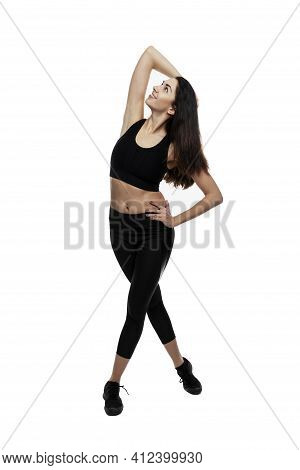 A Young Woman In Black Sportswear Stands And Looks Up. Smiling Beautiful Slim Brunette. Sports And A