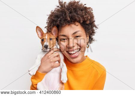 Portrait Of Good Looking Cheerful African American Woman Enjoys Company Of Small Pedigree Dog Wears