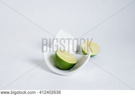 Cut halves Of Lime In A Broken Half Of A Ceramic Small Platter On A White Background. Place For Te