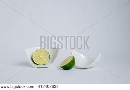 Sliced Cut halves Of Lime In A Broken Half Of A Ceramic Small Platter On A White Background. Place
