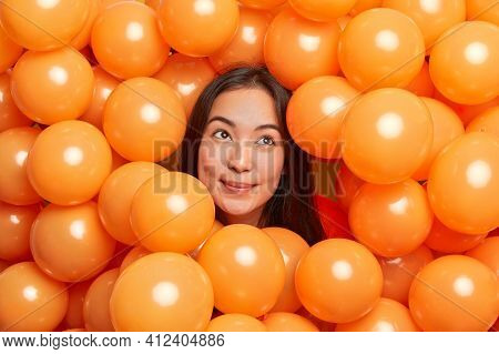 Dreamy Brunette Beautiful Asian Woman Concentrated Above Poses Around Inflated Balloons Thinks About