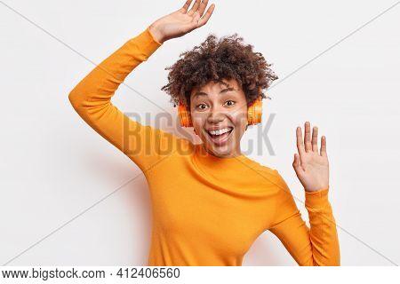 Cheerful Joyful African American Woman Enjoys Awesome Sound Quality Wears Stereo Wireless Headphones
