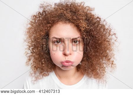 Portrait Of Offended Curly Haired Beautiful Young Woman Blows Cheeks Has Displeased Expression Expre