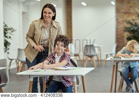 Encourage Kids To Learn. Smiling Young Female Teacher Standing Near Little School Boy During Lesson