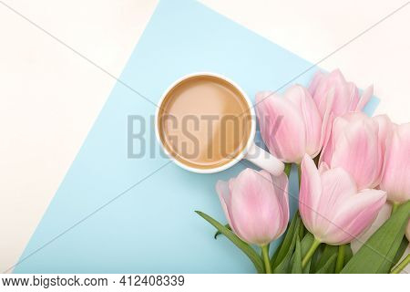 Morning Cup Of Coffee And Beautiful Tulips Flowers On Light Pastel Background, Top View. Cozy Breakf