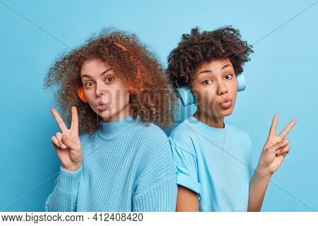 Horizontal Shot Of Two Curly Haired Female Companions Keep Lips Folded Make Peace Gesture Listen Mus