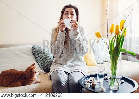 Spring Allergy. Woman Sneezing Because Of Tulips Flowers Surrounded With Pills And Nasal Drops At Ho