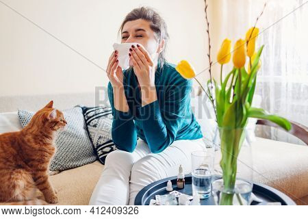 Spring Allergy. Woman Sneezing Because Of Tulips Flowers Surrounded With Pills And Nasal Drops Sitti