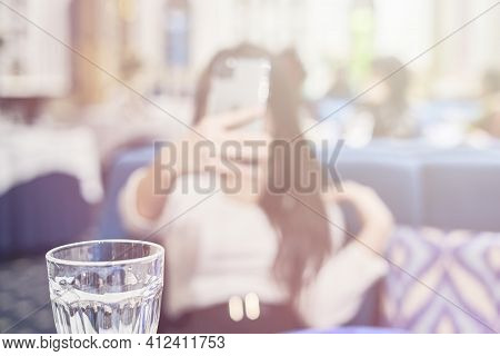 Blurred Shot Of A Girl Doing A Selfie In The Restaurant. Unfocused Image Of A Young Female Taking A