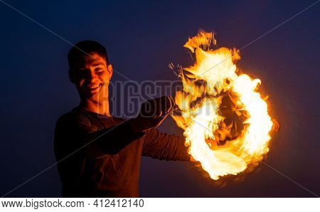 Happy Guy Artist Perform Fire Circle By Spinning Burning Poi On Idyllic Dark Sky At Night Outdoors,