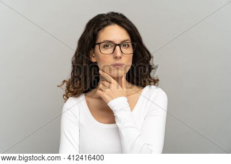 Portrait Of Unsure Doubtful Young Woman Touching Her Chin, Frowning, Pondering, Looking At Camera Do