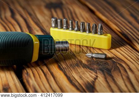 Set of heads (bits) and screwdriver on a wooden table