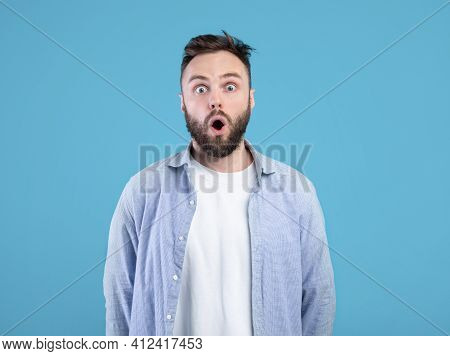 Portrait Of Stunned Young Guy Opening Mouth In Shock On Blue Studio Background
