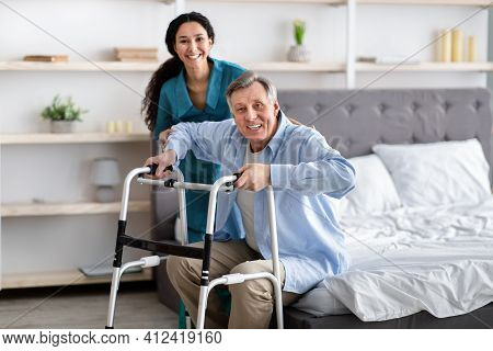 Female Nurse Helping Elderly Male With Walking Frame Stand Up From Bed At Home. Professional Care Fo