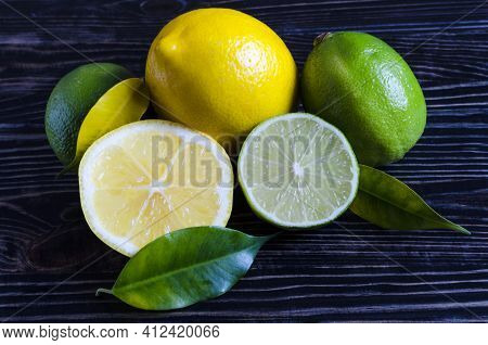 Fresh Green Limes, Yellow Lemons On A Wooden Background Lime And Lemon In A Close-up Section