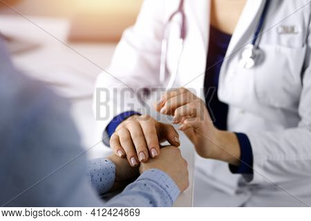Unknown Woman-doctor Is Holding Her Patients Hands To Reassure The Patient, Discussing Current Healt