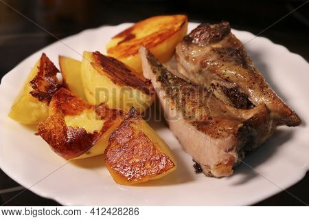 Baked Meat With Potatoes On A White Plate. Appetizing Crispy Crust On Food.