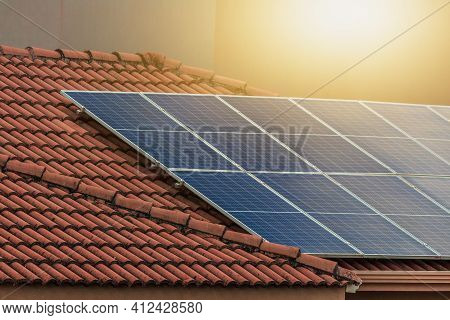 Solar Photovotaic Panel At A Roof At Suset.  Solar Energy House Company Concept Image. Space For Tex
