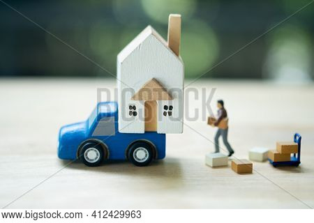 Miniature Worker Moving Thing To Miniature House On Blue Car. Real Estate And Property Business Conc