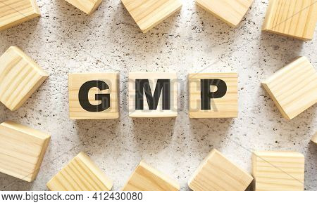 The Word Gmp Consists Of Wooden Cubes With Letters, Top View On A Light Background. Work Space.