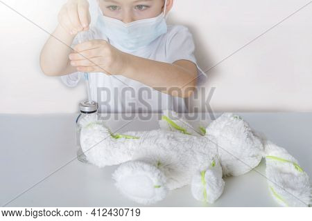 Vaccination And Immunization Of Population Concept. Kid Boy In Medical Protective Mask Plays,  Inocu