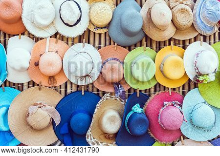 A Variety Of Fashionable And Colorful Hats Hanging On The Bamboo Backdrop Of Curbside Shop.women's D