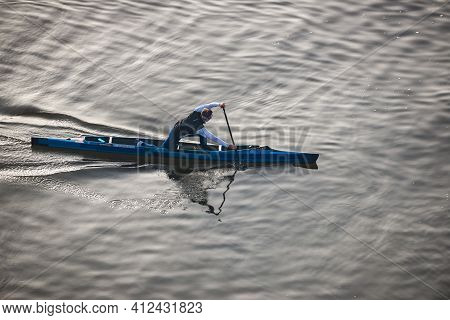 Prague, Czech Republic - February 24, 2021. Aerial View Of Young Man Sailing On Blue Single Canoe In
