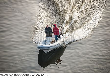 Prague, Czech Republic - February 24, 2021. Speed White Dinghy Boat With Two Man On Board In Winter