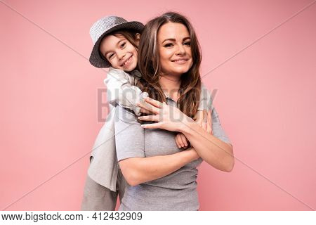 A Charming Girl In A Shirt Hugs A Smiling Mother In A Dress And Wavy Hair. Family Warm Hugs