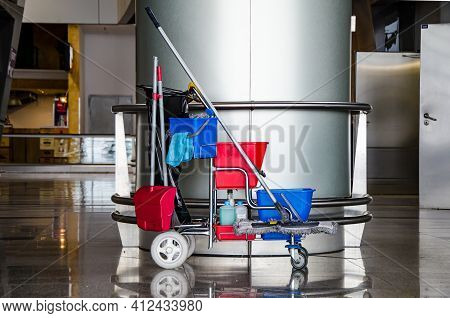 Cleaner Cart In A Public Place. Mobile Cart With Cleaning Products: Mop, Buckets For Cleaning The Fl