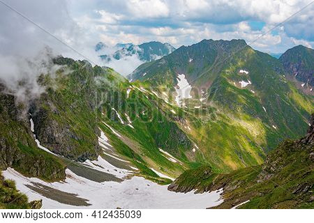 Fagaras Mountain Landscape In Summer. Wonderful Nature Scenery With Clouds On The Peaks And Snow In