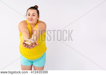 Friendly Large Woman 30s Wearing Illuminating T-shirt Holding Transparent Bowl With Eclairs Cake In