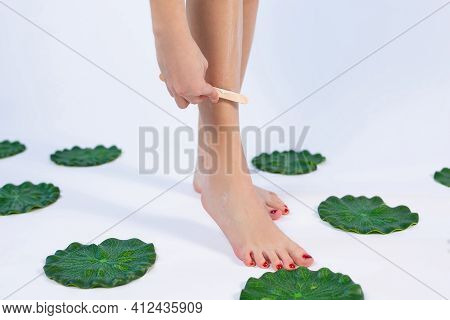 Body Cream And Wooden Spatula On Female Legs. Cropped Photo Of Woman Legs In Hair Removal Process. F