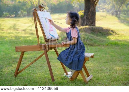 A Little Girl Is Sitting On The Wooden Bench And Painted On The Canvas Placed On A Drawing Stand