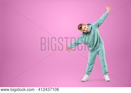 Little In A Turquoise Suit Posing And Fooling Around On A Pink Background, Looking At The Camera. Ch