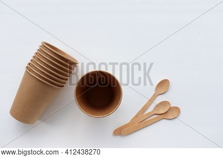 Kraft Paper And Wooden Kitchen Utensils On Table. Recycled And Sustainable Products On White Backgro