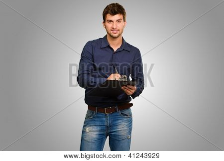 Young Man Writing On Clipboard Isolated On Grey Background