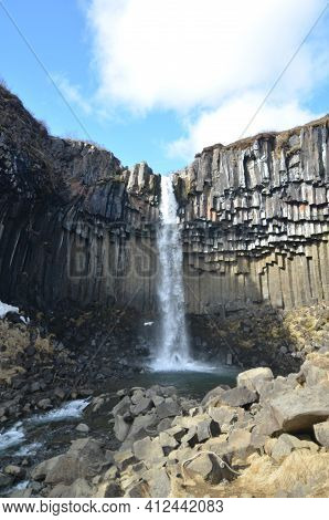 Scenic Views Of A Basalt Column Waterfall In Iceland