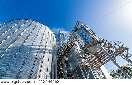 Grain Elevators For Crop Storage. Metal Bridge From The Roof Of Metal Tank. View From Below. Closeup