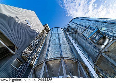 Metal Grain Elevators On Modern Factory. Crop Storage In Factory. Selective Focus On Steel Construct