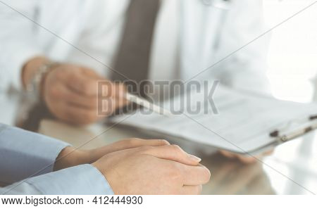 Unknown Male Doctor And Woman-patient Discussing Current Health Examination While Sitting In Clinic