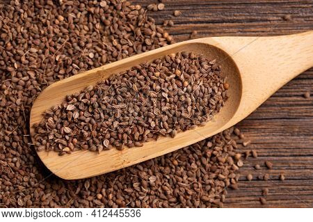 Anise Seeds In A Large Wooden Spoon. Scattered Anise Seeds. Dried Anise On A Wooden Table Surface.